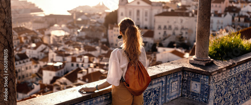 obraz PCV Blonde woman standing on the balcony and looking at coast view of the southern european city with sea during the sunset, wearing hat, cork bag, safari shorts and white shirt