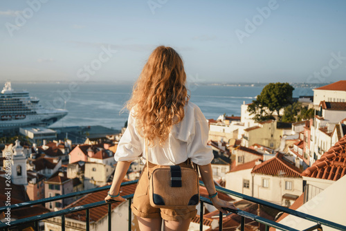 Foto Blonde woman standing on the balcony and looking at coast view of the southern e