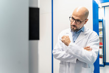Man Wearing Lab Coat And Glasses Looking At Machine