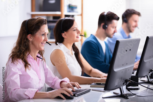 Photo Smiling Customer Service Executives Using Earphones