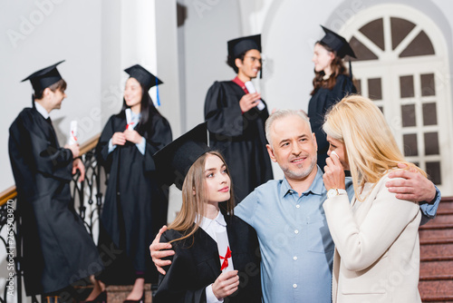 Obraz selective focus of attractive girl in graduation cap looking at crying mother while hugging with father near students - fototapety do salonu
