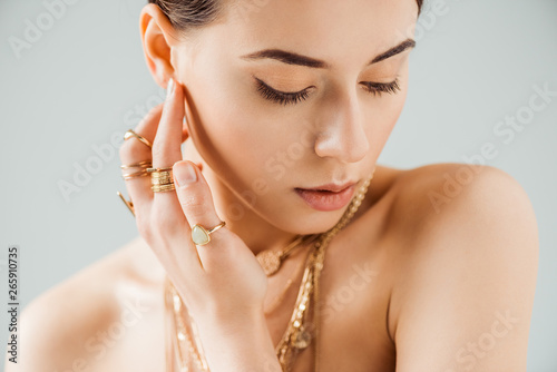 young naked woman with shiny makeup in golden necklaces and rings isolated on gr Tapéta, Fotótapéta