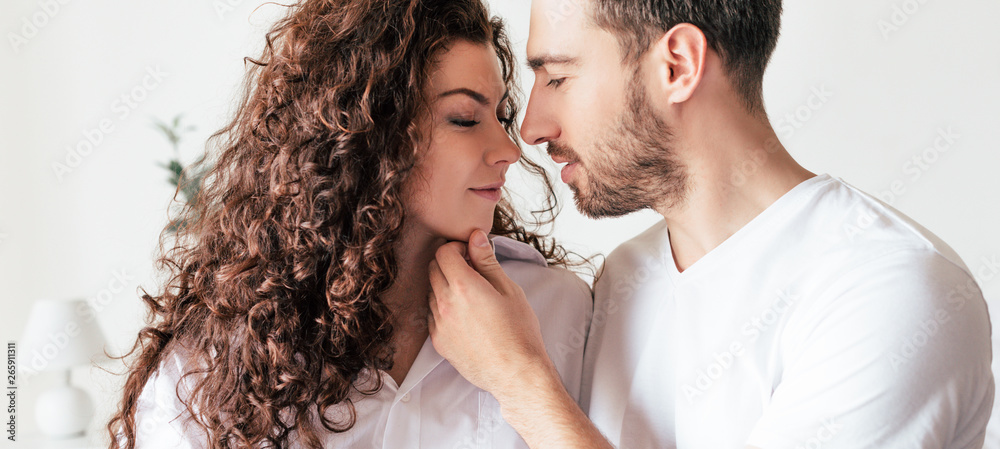Fototapeta panoramic shot of handsome bearded man gently touching girlfriend at home