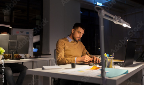 Aluminium Prints Personal business, technology, design and people concept - young creative man or graphic designer with laptop computer working by pen tablet late at night office