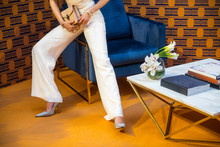 High Fashion Model Wearing White Pants And Silver High Heels Holding A Bag With Jewellery