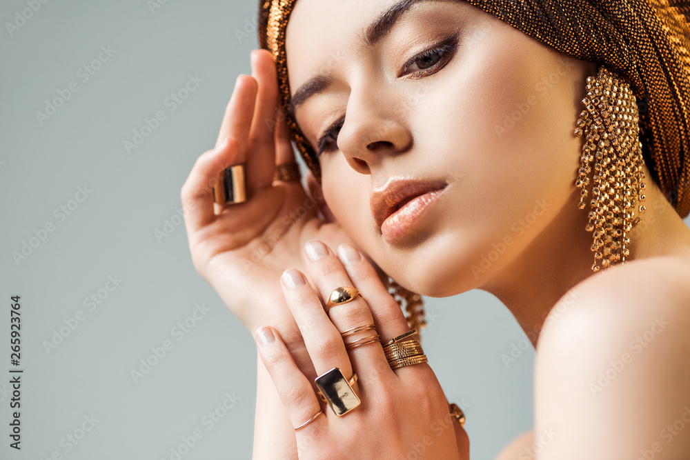 Fototapeta young tender naked woman with shiny makeup, golden rings and earrings in turban isolated on grey