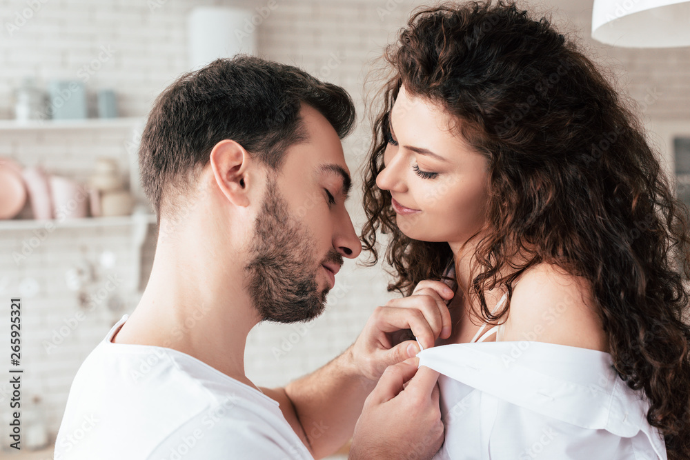 Fototapety, obrazy: smiling bearded man undressing curly girlfriend at home