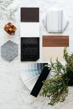 Top View Of Material Selections Including Granite Tile, Marble Tile, Acoustic Tile, Walnut And Ash Wood Laminate And Painted Color Tone Album With Plant And Flowers On Marble Top Table.