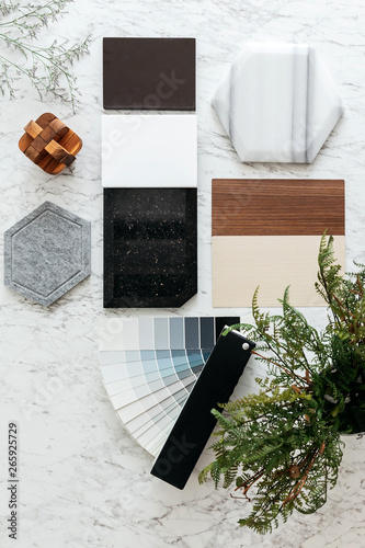 Fotomural Top view of Material Selections including Granite tile, Marble tile, Acoustic tile, Walnut and Ash Wood Laminate and Painted color tone album with plant and flowers on marble top table