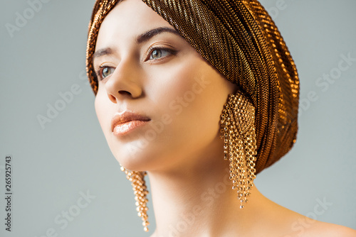 Obraz na płótnie young naked woman with shiny makeup, golden rings in turban looking away isolate