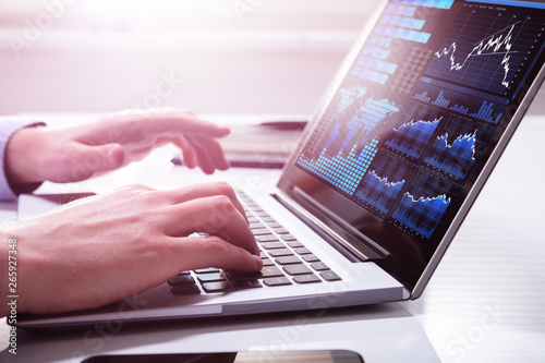Stock Market Broker Analyzing Graph On Laptop