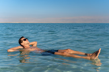 Young Man Floating On The Water Surface Of The Dead Sea