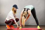 Woman in sportswear stretching legs with trainer - 265940314
