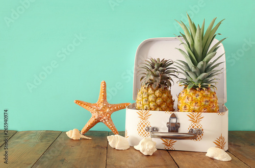 Recess Fitting India Ripe couple pineapple in suitcase over wooden table or deck. Tropical summer vacation concept