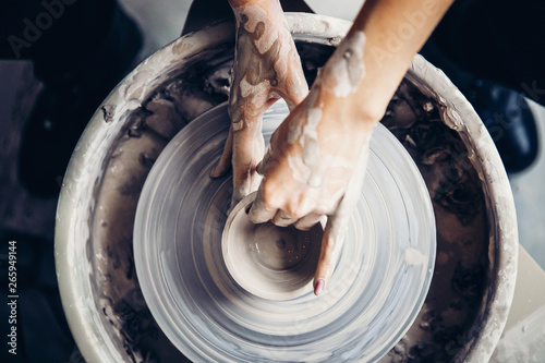 Young woman in red apron works behind potter wheel with length, making handmade plate. Concept of concentration, Top view