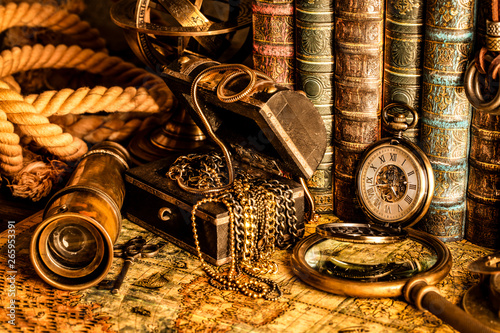 Obraz na plátně Antique clock on the background of a magnifying glass, treasure chest with gold and books