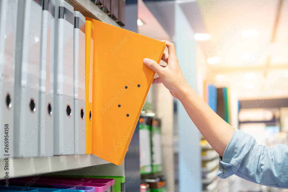 Fototapeta Male hand choosing new orange ring binder file folder from colorful shelf display in stationery shop. Buying office supplies concept