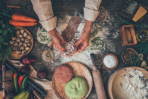 Fototapety, obrazy: Female hands making fresh homemade pasta. Colored raw vegetable pasta with beets, carrots and spinach. Pasta ingredients and farmers vegetables on the dark wooden table top view.
