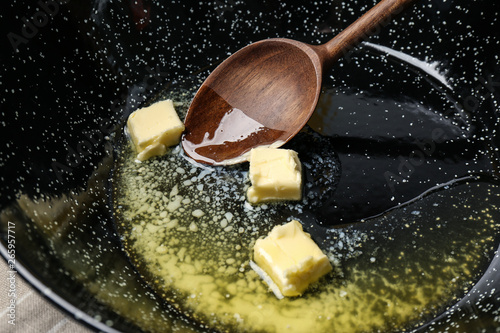 Fotografía  Frying pan with melting butter and wooden spoon, closeup