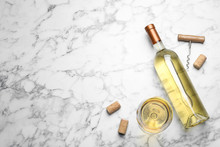 Glass And Bottle With White Wine On Marble Background, Flat Lay. Space For Text