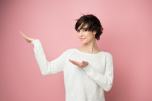 Charming Stylish Young Woman Pointing At Copy Space And Smiling At Camera. Cute Girl Displays Something Over Soft Pink Background.