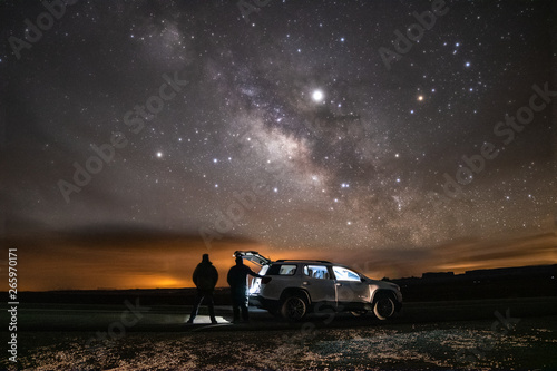 Photo sur Toile Marron chocolat Two silhouettes of people standing under the Milky Way stretching across the night sky. Adventure scene next to a vehicle in a remote location.