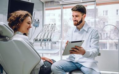 Ludzi, medycyny, stomatology i opieki zdrowotnej pojęcie, - szczęśliwy męski dentysta pokazuje pastylka komputer kobieta pacjent przy stomatologicznym kliniki biurem.