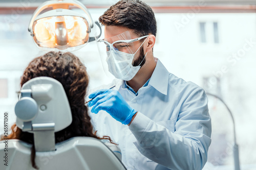 Photo Dentist working in dental clinic with patient in the chair.