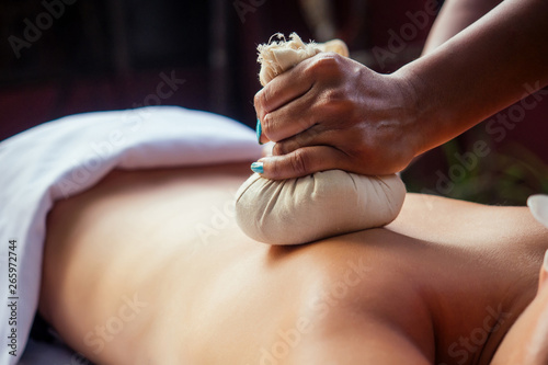 Portrait of young beautiful woman lying on a wooden table in spa environment flo Fototapeta