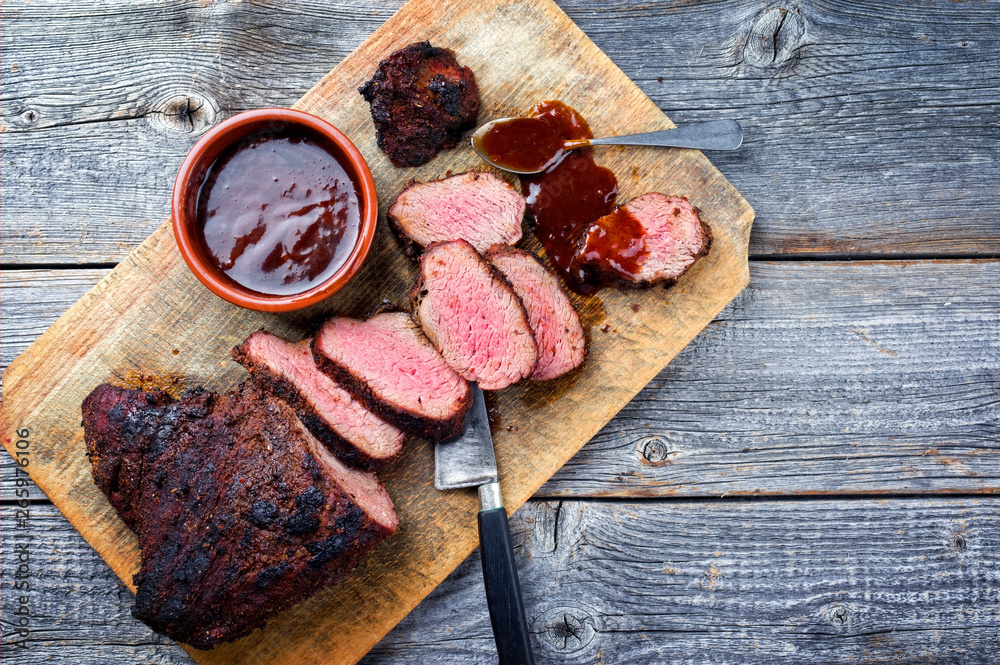 Fototapety, obrazy: Barbecue dry aged wagyu tri tip steak with BBQ sauce as dip as top view on a wooden cutting board with copy space
