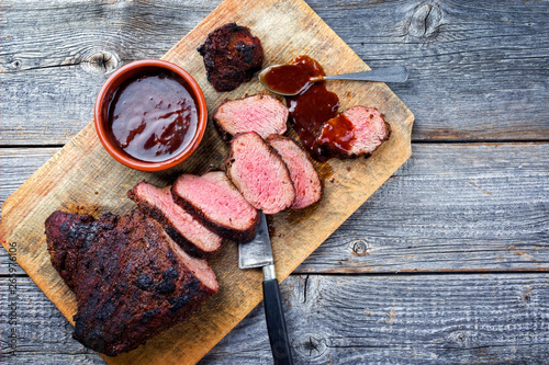 Recess Fitting Steakhouse Barbecue dry aged wagyu tri tip steak with BBQ sauce as dip as top view on a wooden cutting board with copy space