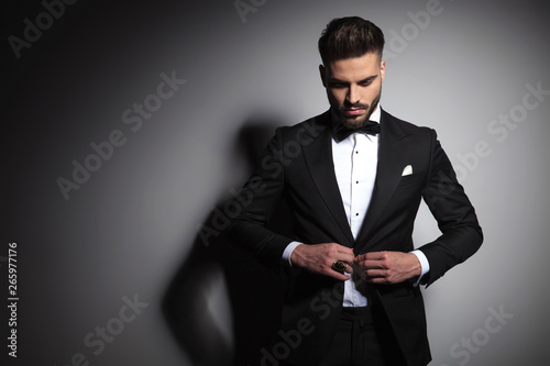 Obraz na płótnie caucasian man in black tuxedo buttoning his suit