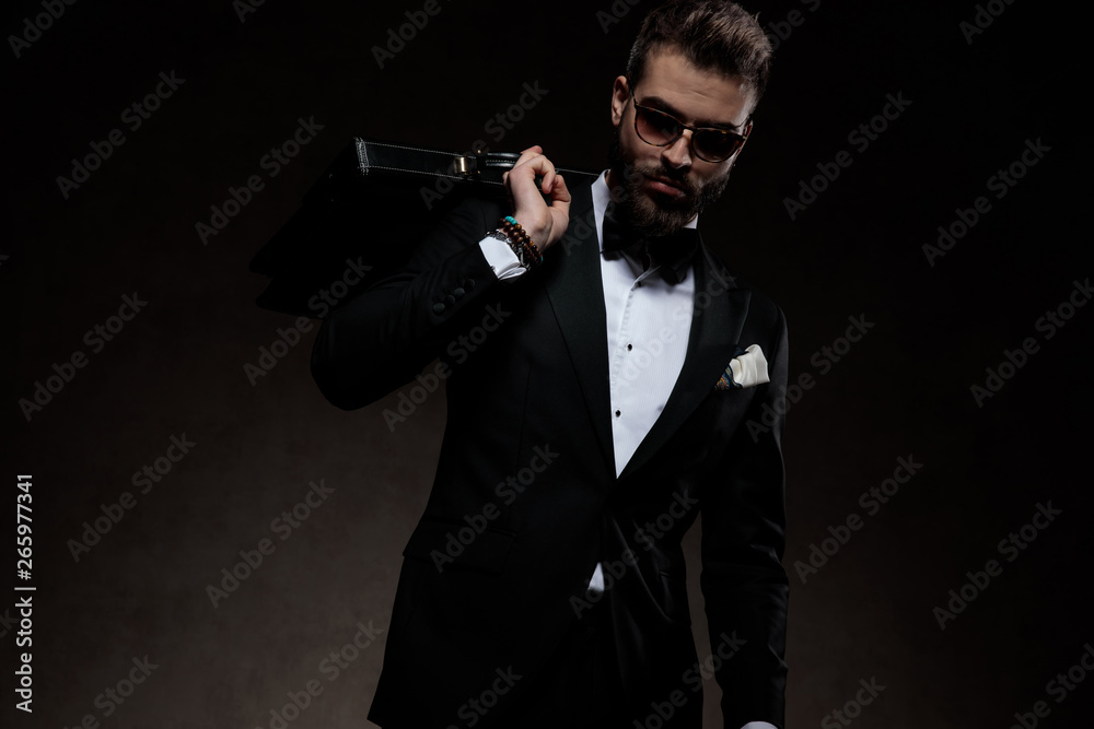 Fototapeta dramatic  man in tuxedo and sunglasses holds briefcase on  shoulder