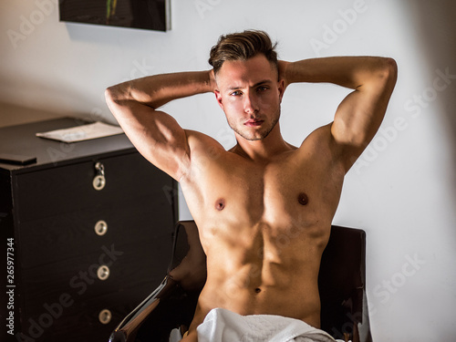 Canvas-taulu Shirtless naked sexy male model sitting alone on chair in his bedroom, looking a
