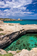 Archaeological site and tourist resort of Roca Vecchia, Puglia, Salento, Italy. Turquoise sea, clear blue sky, rocks, sun, in summer. The Cave of Poetry. The lookout tower in the background.