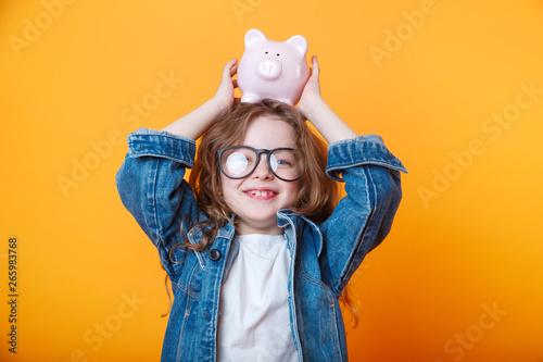 Pinturas sobre lienzo  Cute little girl in eyeglasses shaking piggy box on orange background