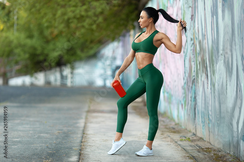 Beautiful fitness woman with shaker outdoors. Slim athletic girl in the stadium, abs flat belly