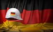 Leinwandbild Motiv White hard hat laying over Germany flag. Construction and employment in Germanyconcept, .