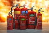 Fototapeta Panels - Fire extinguishers on a fire background. Various types and different sizes of extinguishers. 3d illustration