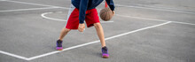 Young Basketball Player Training To Dribble Outdoor On The Asphalt Court In Summer Seasons