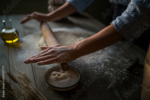 Aluminium Prints Mills Homemade raw dough on a rustic wooden table. Making pizza. Dough with a rolling pin. Flour, butter, wheat spikelets. Concept of cooking and food. Toned image.