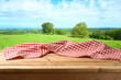 Leinwandbild Motiv Empty wooden table with tablecloth over summer meadow background