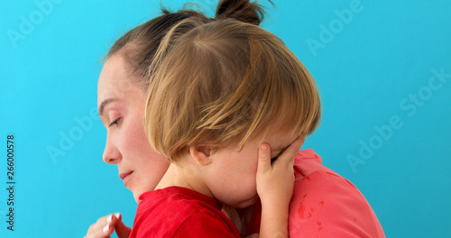 Mother calms baby on blue background Canvas Print