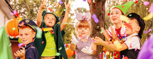 Panoramic View Of Animator And Kids Enjoying Confetti Rain During Birthday Dressing Up Party In The Garden