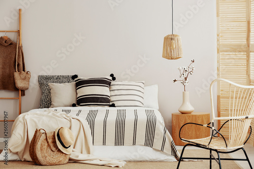 Fototapety, obrazy: Striped bedding on comfortable king size bed in contemporary bedroom interior with wicker chair and copy space on empty wall