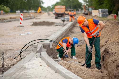 Two workers in orange safety jacket on a road construction, industry and teamwork