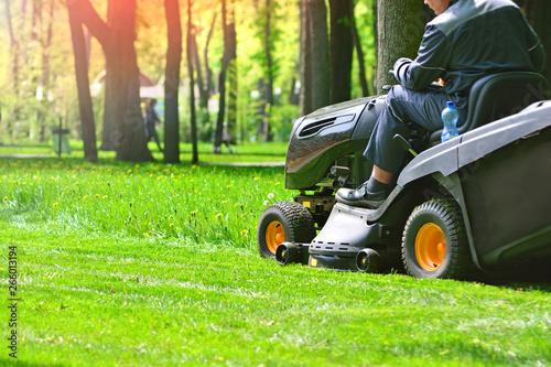 Foto auf Gartenposter Lime grun Professional lawn mower wirh worker cut the grass