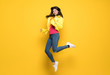 Teenager girl jumping over isolated yellow wall