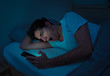 Young caucasian sleepless man bored in bed surfing on the Internet addicted to mobile phone