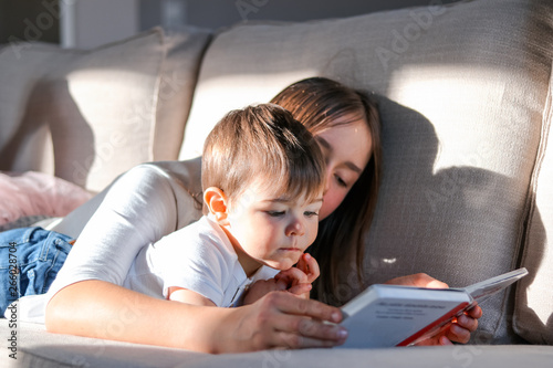 Photo  Siblings reading book together on couch